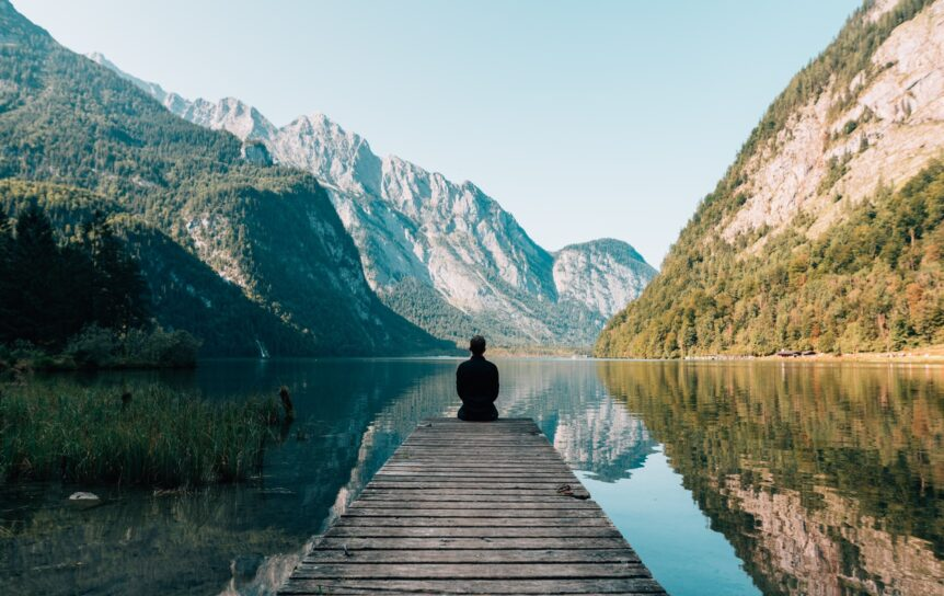 A man sitting in front of a lake relaxing, hosted by Wellin5.