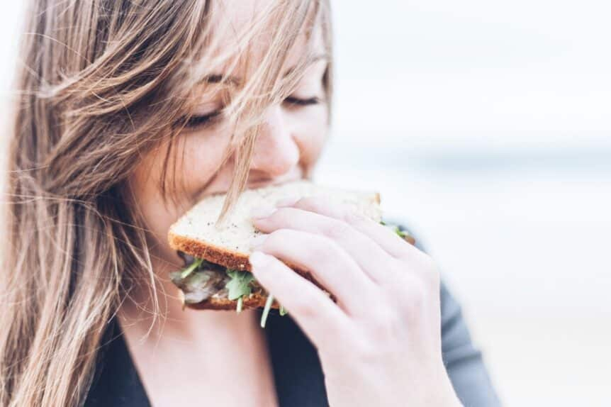 A woman with windswept hair biting into a sandwich, hosted by Wellin5