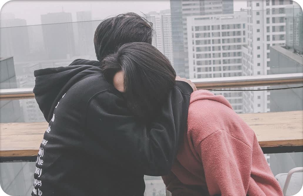 Man hugging woman on balcony