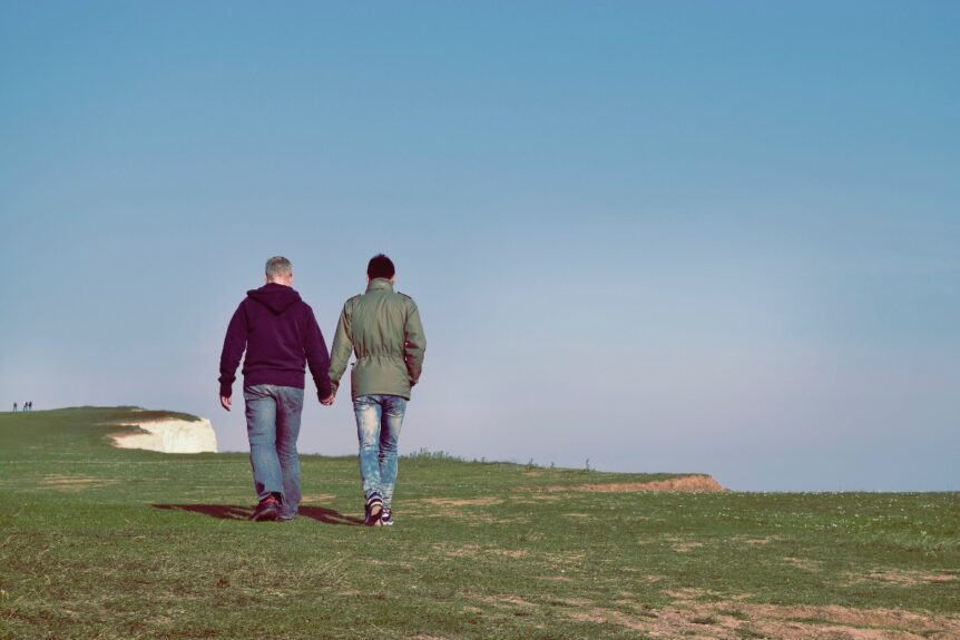 A gay couple in the LGBTQIA2+ community walking through a field and holding hands.